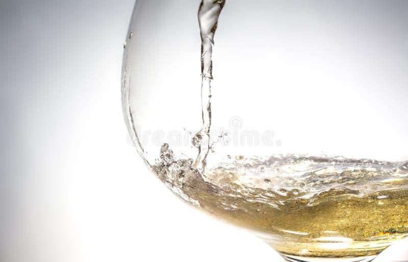 涌入玻璃特写镜头,酒,飞溅,泡影,嘶嘶响的酒小河  免版税库存照片