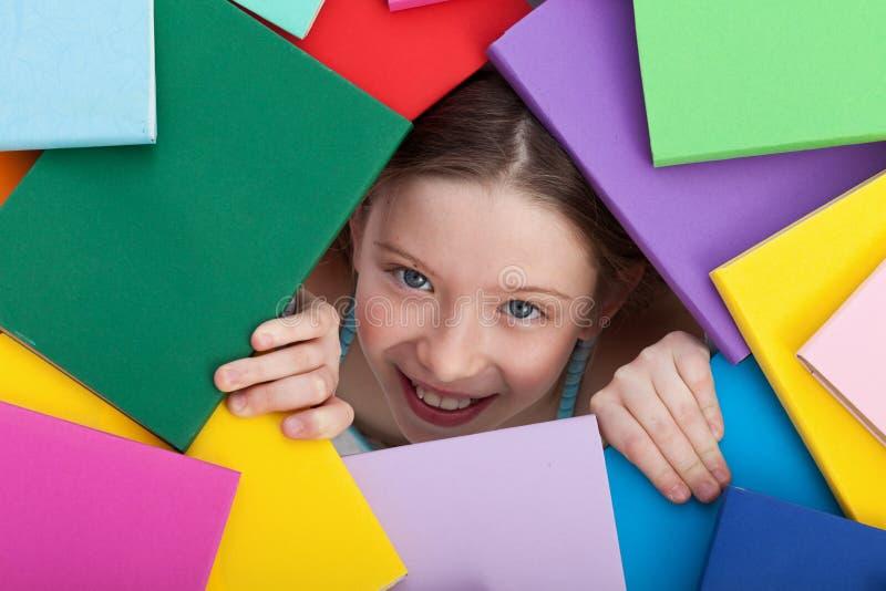 涌现从在书之下的女孩 免版税图库摄影