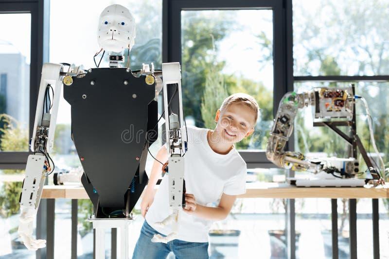 涌现从一个人的机器人的后面金发男孩 免版税库存图片