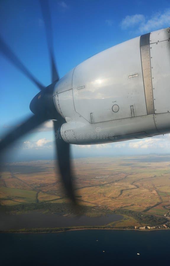 涡轮支柱引擎在飞行中在海洋和海岛海岸线 免版税库存照片