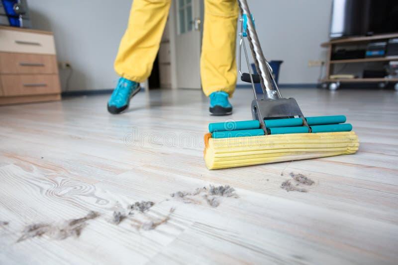 洗涤与刷子拖把的人木地板 免版税库存照片