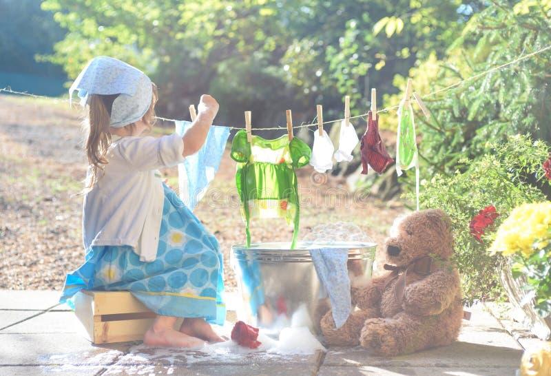 洗涤她的玩具的赤足女孩在洗衣盆附近穿衣 库存图片