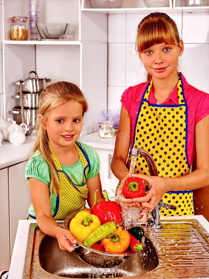 洗涤果子的孩子在厨房 免版税库存照片