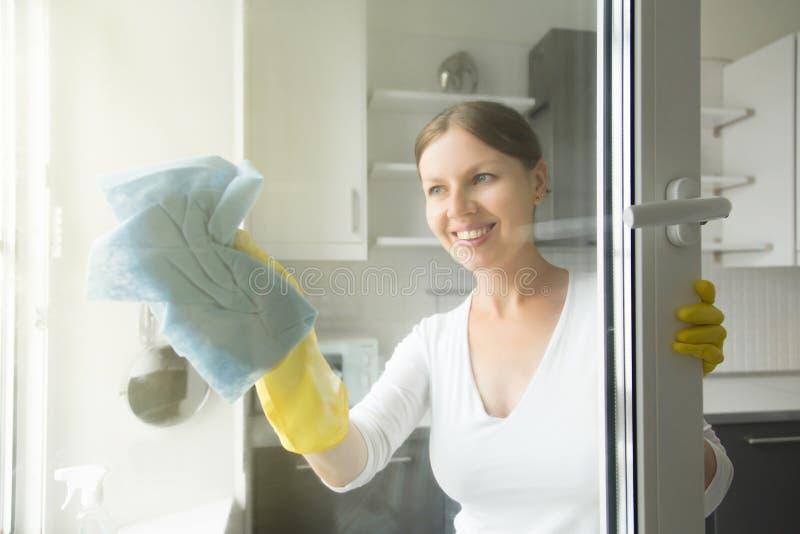 洗涤窗口的美丽的微笑的年轻主妇 免版税库存照片