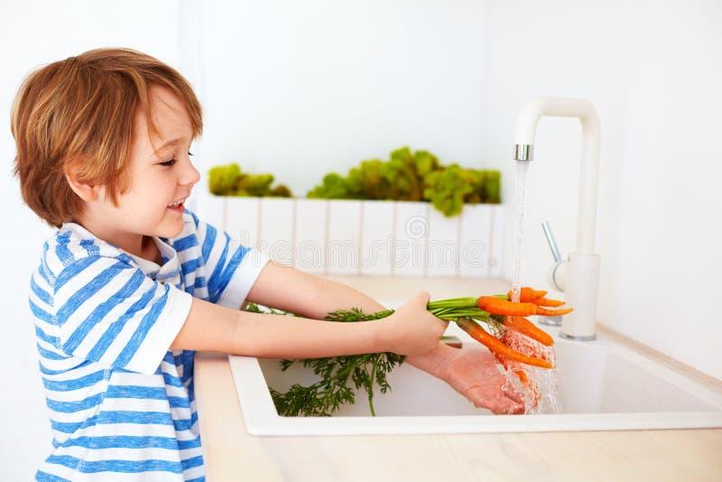 洗涤红萝卜的逗人喜爱的年轻男孩在自来水下在厨房里 免版税库存图片