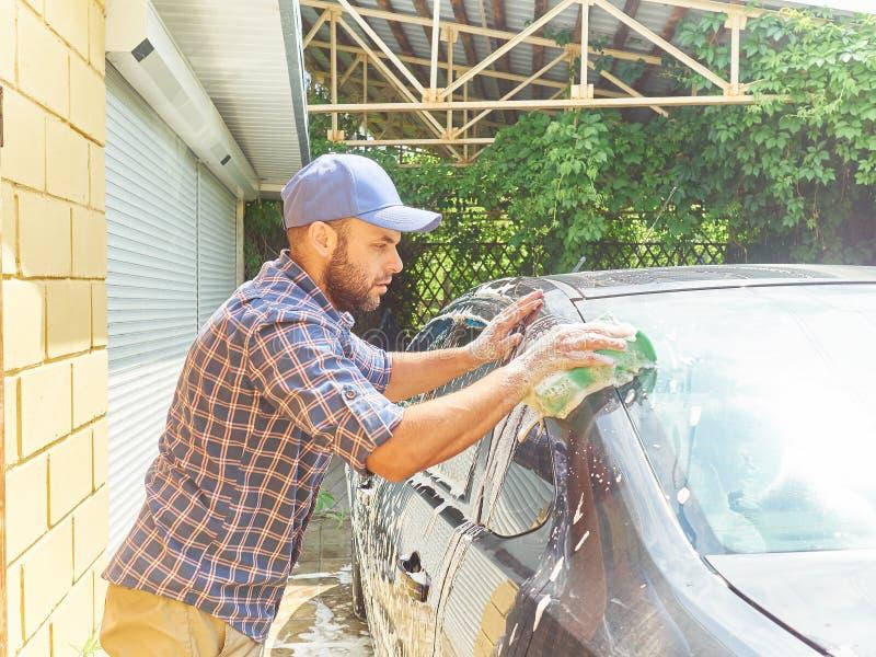 洗涤他的黑汽车的人在房子附近 库存图片