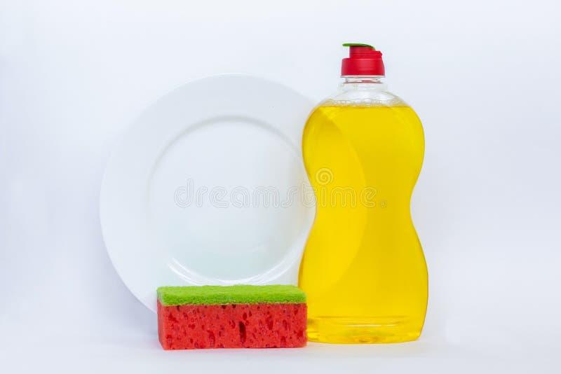 洗涤黄色液体,干净的瓶,干净的板材的厨具和 免版税库存图片
