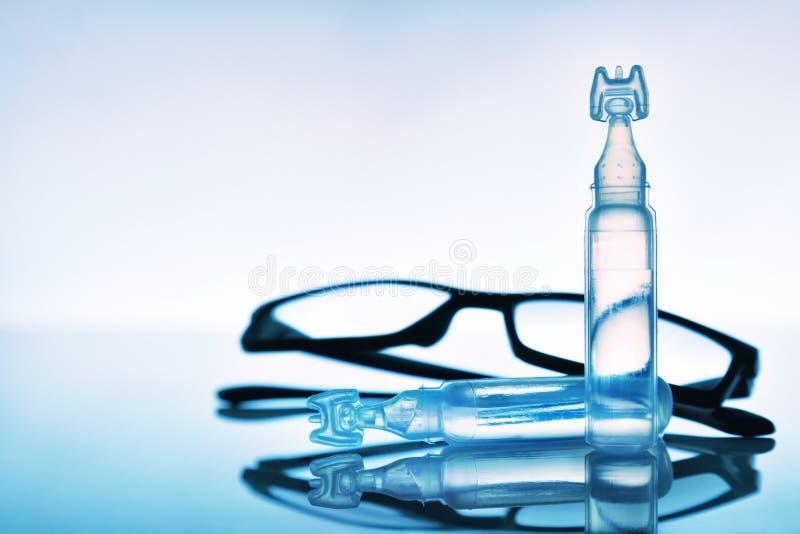润滑剂与眼睛玻璃和蓝色背景构成的眼药水 库存图片