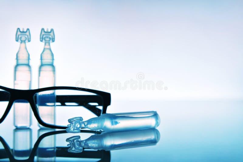 润滑剂与眼睛玻璃和蓝色背景的眼药水 库存图片