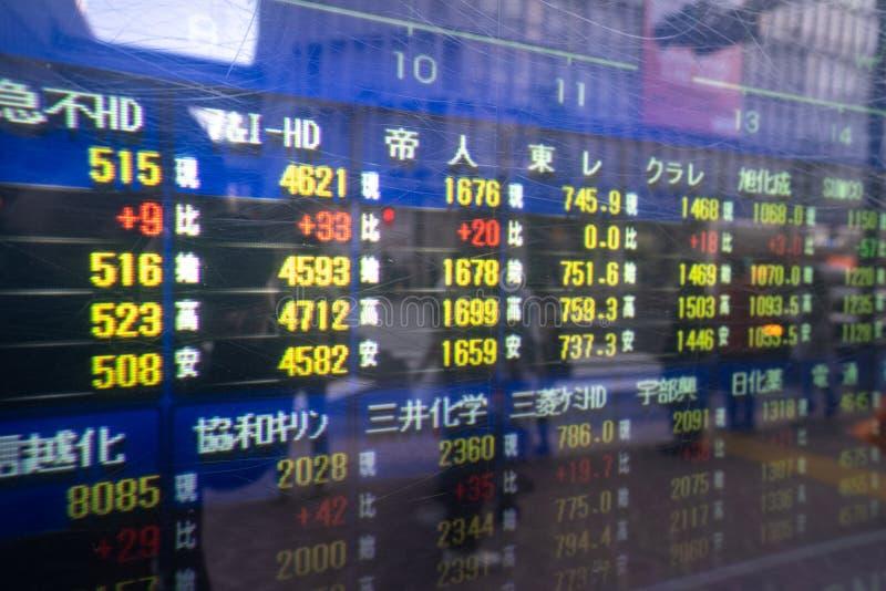 涩谷,东京,日本- 2018年12月26日:走的人和skycrapper在显示器的办公楼的反射与股票 库存图片