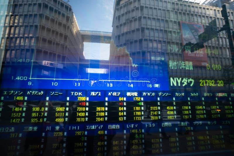 涩谷,东京,日本- 2018年12月26日:skycrapper在显示器的办公楼的反射与与图表的股票市场市场价 库存图片