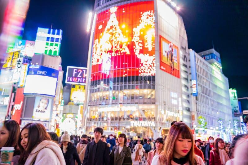 涩谷,东京,日本- Decembe 24日2018年:人群进来在斑马行人穿越道的步行者人在涩谷区在晚上 免版税图库摄影