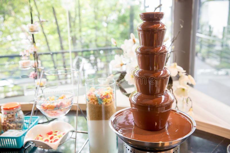 涮制菜肴的巧克力喷泉 瑞士人甜点  浸洗的巧克力融解 背景的图象 免版税图库摄影