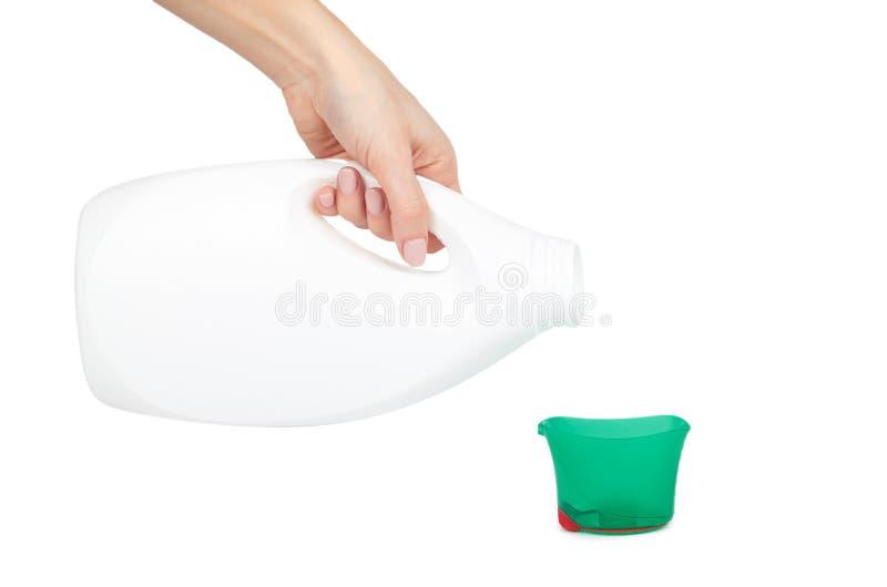 液体洗涤剂的量杯用手,隔绝在白色背景 免版税库存图片