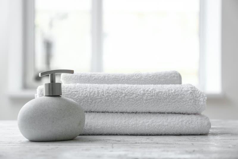 液体皂和被折叠的白色特里毛巾在桌上户内 免版税库存照片