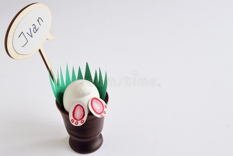 淘气复活节兔子,有孩子的名字的轻便短大衣陶瓷花瓶的有绿草的由纸制成在轻的背景 最小 免版税图库摄影