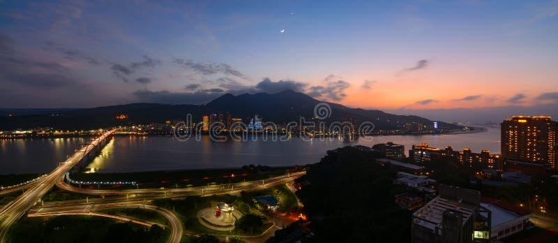 淡水厅和巴厘岛区的全景沿河的在日落的新北市与新月形月亮和行星金星r 图库摄影
