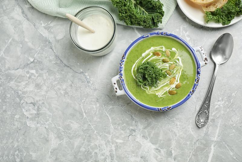 淡灰色大理石桌上供应美味的羽衣甘蓝汤 文本的空格 免版税库存照片