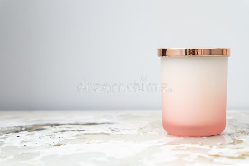 淡粉红色和白色ombre蜡烛瓶子有一个发光的金盒盖的,坐床头柜夜立场 蜡烛没有被点燃 ?? 图库摄影