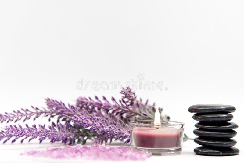 淡紫色与岩石和蜡烛的芳香疗法温泉 泰国温泉放松治疗和按摩白色背景 免版税库存照片