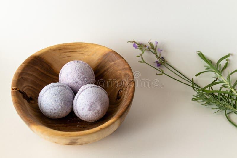 淡紫色在一个木碗的浴炸弹有淡紫色切口的 库存照片