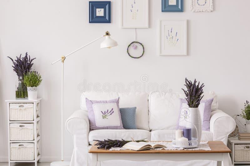 淡紫色在内阁开花在灯和白色沙发旁边在客厅内部与桌和海报 实际照片 免版税库存图片
