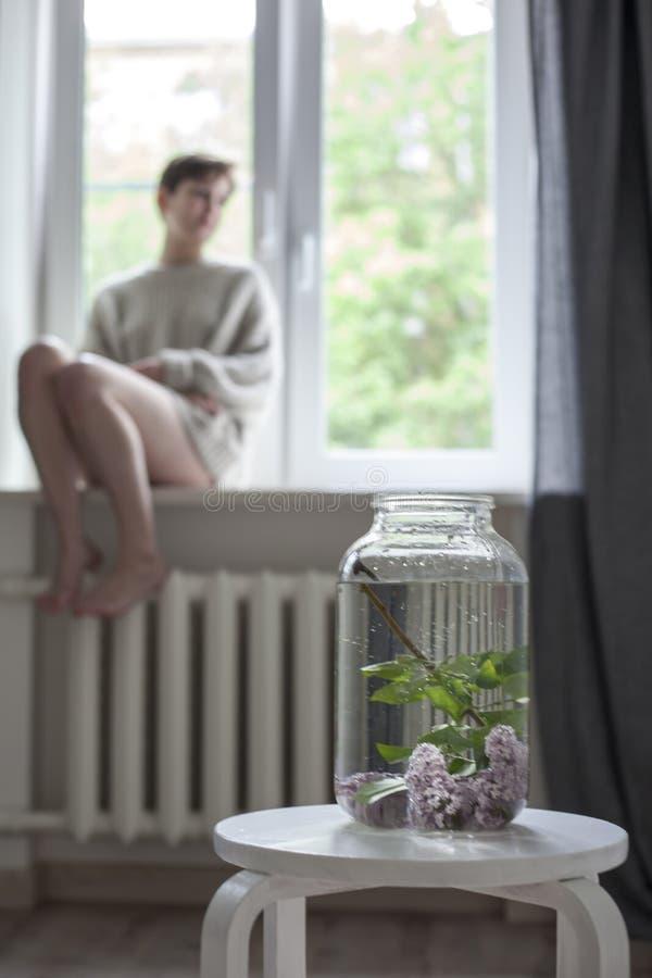 淡紫色枝杈花束在一个透明瓶子的在白色椅子作为内部的装饰 女孩坐窗口 免版税图库摄影