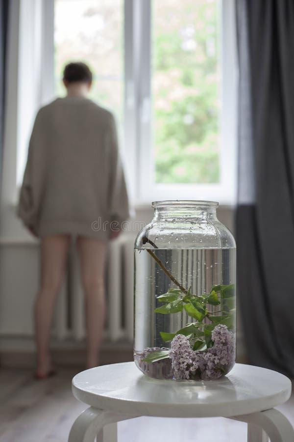 淡紫色枝杈花束在一个透明绿色瓶子的在白色椅子作为内部的装饰 免版税库存图片