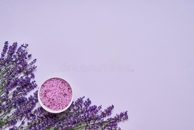 淡紫色温泉 淡紫色花和腌制槽用食盐在碗在淡紫色背景 E E 库存照片