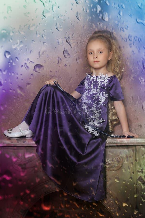淡紫色礼服的小公主金发碧眼的女人 免版税库存图片