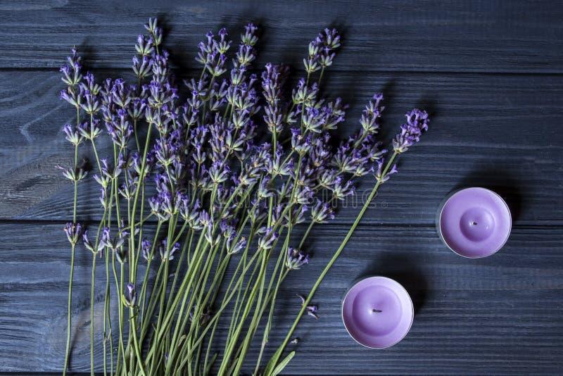 淡紫色花和紫罗兰色蜡烛在一张深蓝木桌上 免版税库存照片