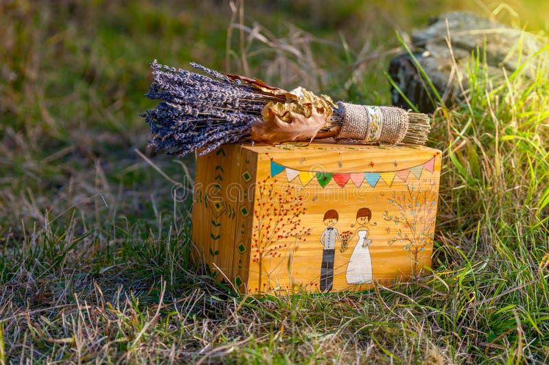 淡紫色花婚礼花束在一个手工制造箱子顶部的 库存图片