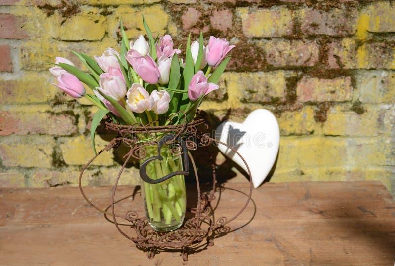 淡色与心脏的郁金香花束在葡萄酒铁丝网筐 库存图片