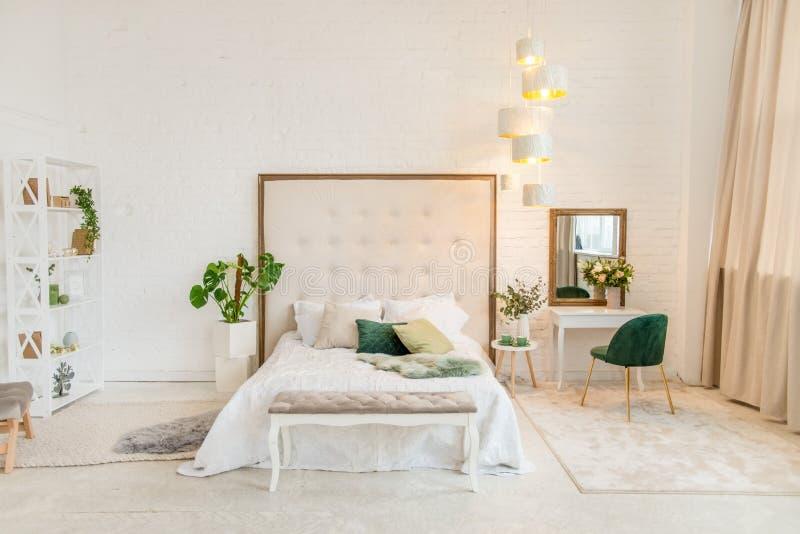 淡色卧室内部的真正的照片与一个双人床的,梳妆台,椅子 酒店房间 免版税库存图片