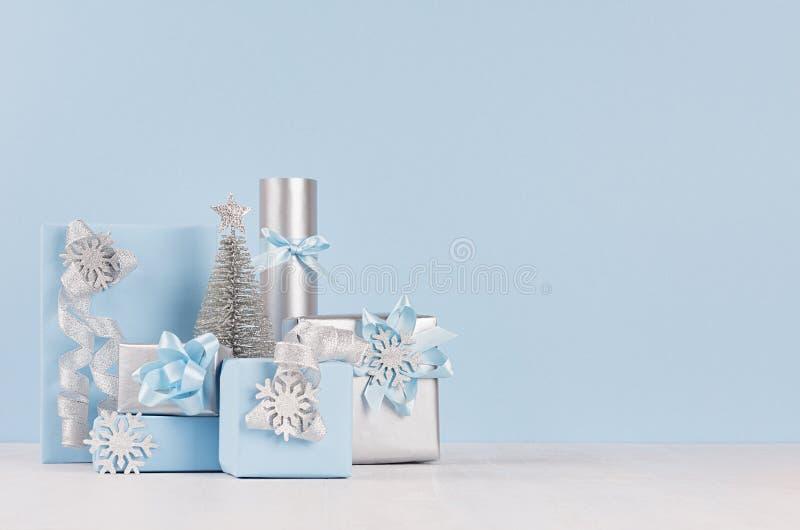 淡色软的蓝色圣诞节背景-装饰和不同的礼物与发光的丝带和弓在白色木桌和蓝色上 库存图片
