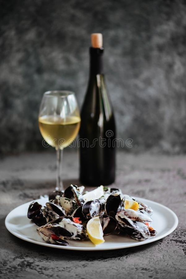淡菜在白酒调味汁煮沸了,供食用多士和柠檬 图库摄影