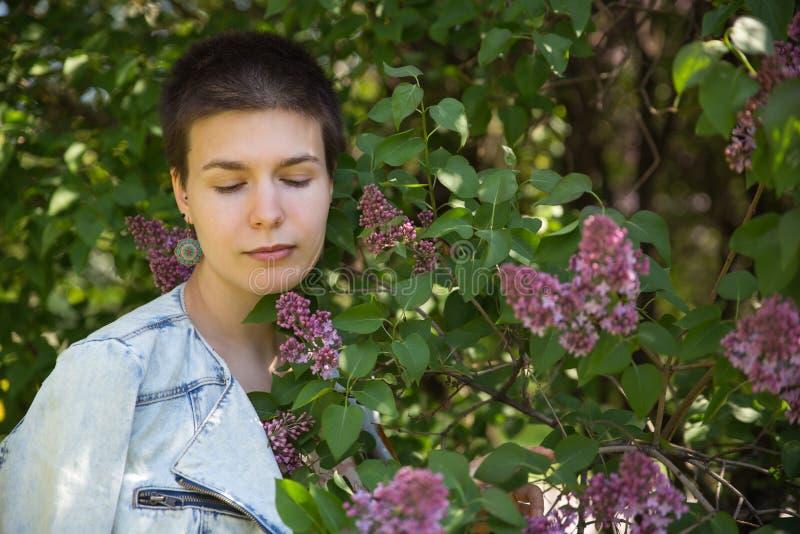 淡紫色开花的树的美丽的逗人喜爱的女孩 库存照片