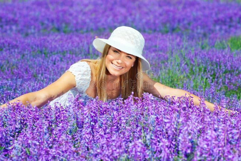 淡紫色领域的俏丽的妇女 免版税库存照片