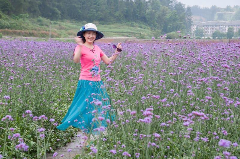 淡紫色领域的俏丽的妇女 免版税库存图片