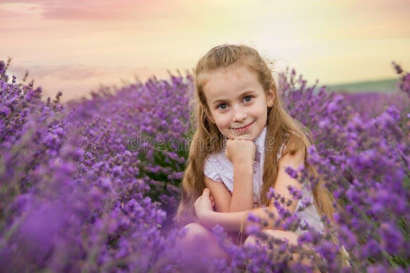 淡紫色领域的女孩在日落 库存照片