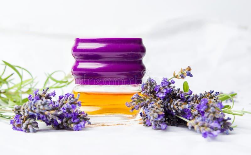 淡紫色香水和花在白色织品 免版税库存照片