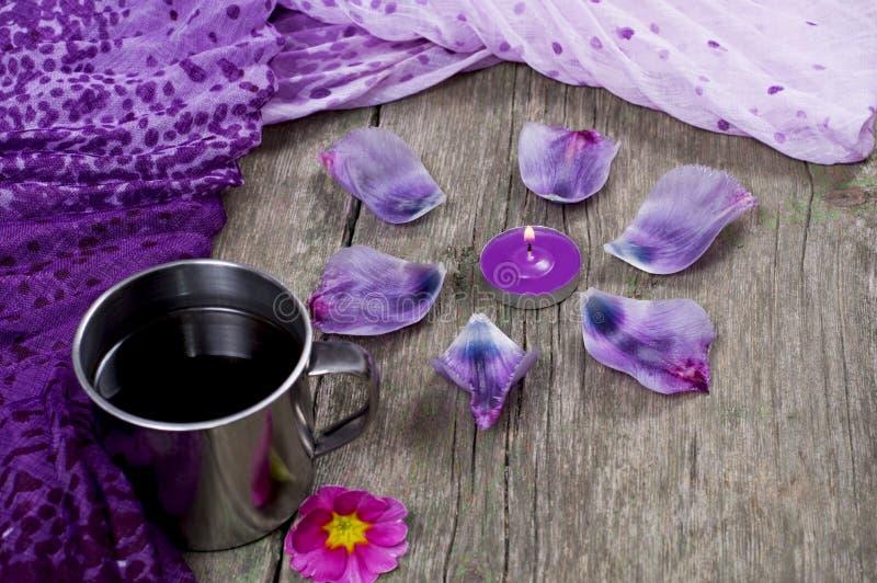 淡紫色围巾、咖啡和用瓣装饰的淡紫色蜡烛 库存图片