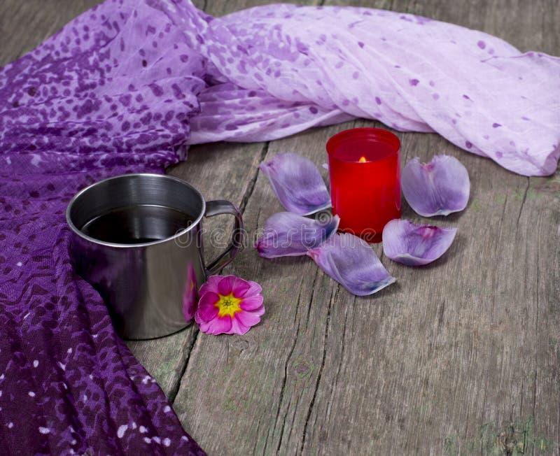 淡紫色围巾、杯子、红色蜡烛和瓣 免版税库存图片