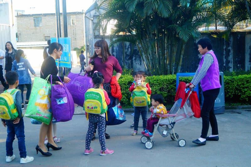深圳,中国:一个年轻母亲采取她的从幼儿园的儿童家 免版税库存图片