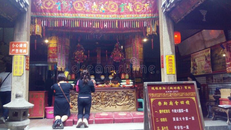 深圳,中国:年轻女人烧香火和崇拜在beidi寺庙 库存照片