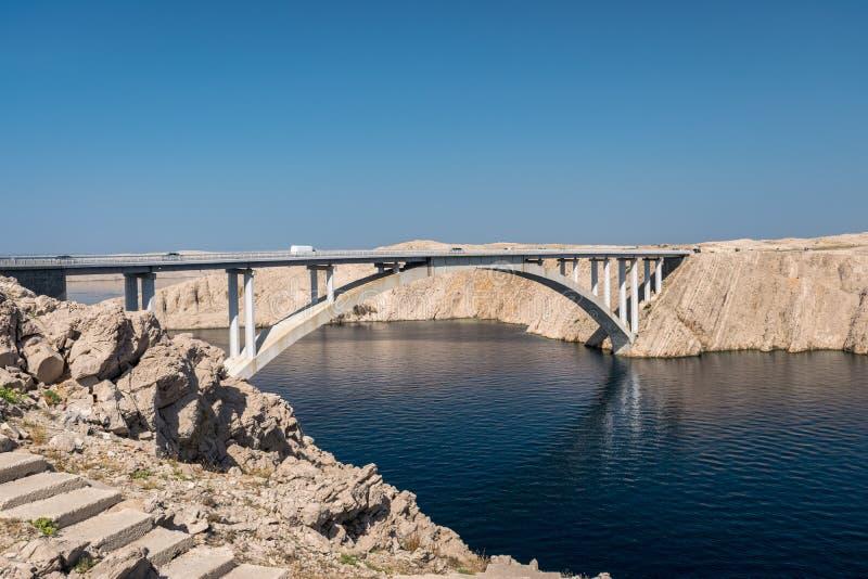 深大海和岩石风景与用克罗地亚的主要土地连接Pag小岛的桥梁 免版税库存图片