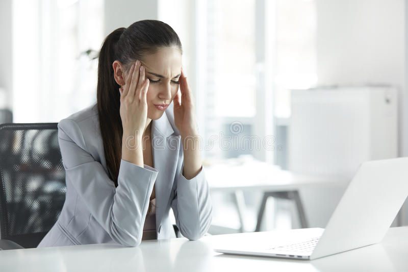 深度服务台领域重点玻璃头疼办公室专业浅开会重点强调疲乏的妇女工作年轻人 年轻女商人画象在 免版税图库摄影