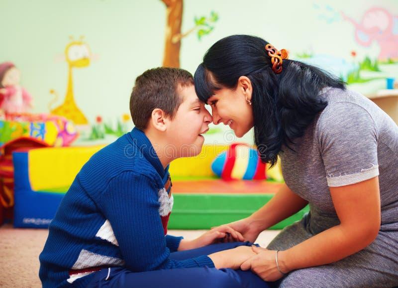 深情的片刻 母亲和她心爱的儿子画象以伤残在康复中心 库存照片