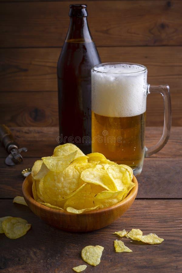 深木背景中的碗里放着一杯啤酒、薯片 把轻啤酒倒进玻璃杯 免版税图库摄影