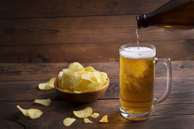 深木背景中的碗里放着一杯啤酒、薯片 把轻啤酒倒进玻璃杯 库存图片
